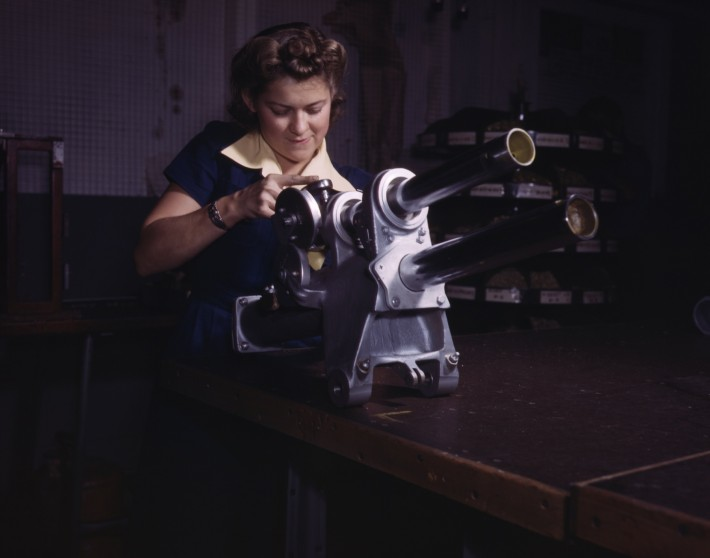 A_young_woman_employee_of_North_American_Aviation,_Incorporated,_working_over_the_landing_gear_mechanism_of_a_P-51_fighter_plane,_Inglewood,_Calif