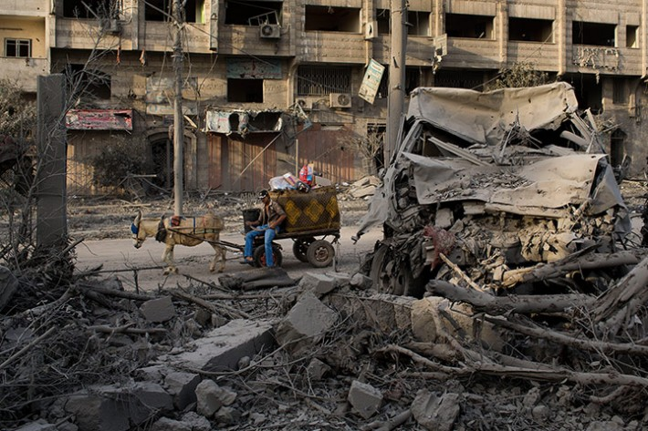 A Palestinian man rides past a destroyed area