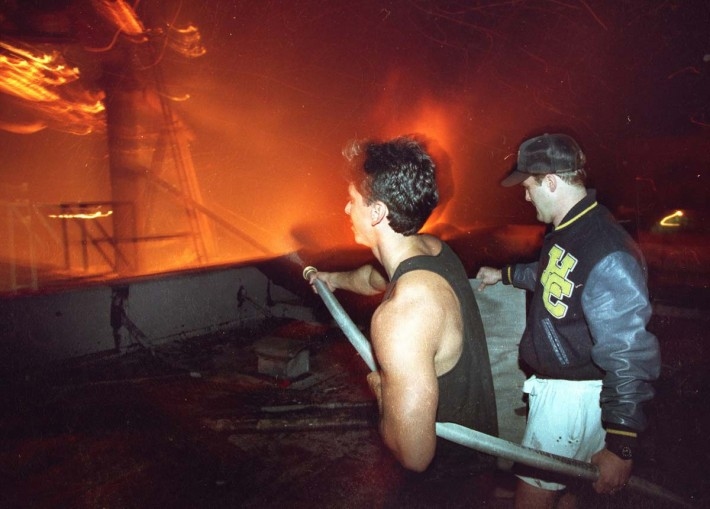 Residents fight fire with a water hose from an apartment building during the third night of the Los Angeles Riots in Koreatown, Los Angeles