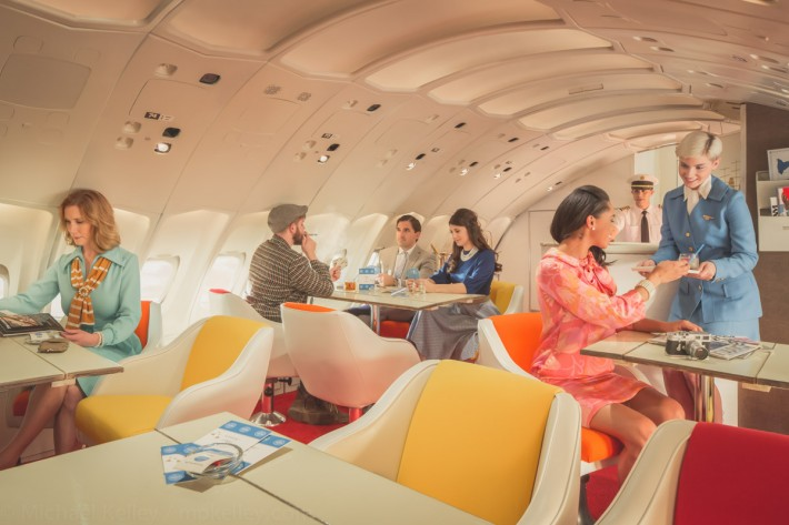 After dinner, passengers are free to roam around the plane. Many take to the upstairs lounge - a signature feature of Pan Am's 747 fleet - where they can relax with drinks, cigarettes, table games and enjoy conversations with fellow travelers while enjoying the view of the sun skipping across the horizon at 35,000 feet.