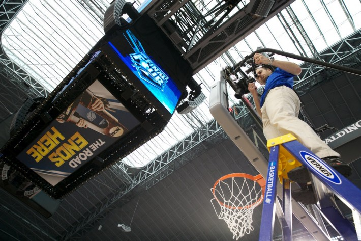 Brett Wilhelm adjusts a basketball backboard camera for NCAA Photos on assignment at the 2014 Men's  Basketball Final Four in Dallas, TX. ©Rudolfo Gonzalez/NCAA Photos