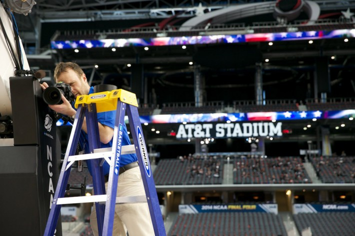 Brett Wilhelm adjusts a basketball stanchion camera for NCAA Photos on assignment at the 2014 Men's  Basketball Final Four in Dallas, TX. ©Rudolfo Gonzalez/NCAA Photos